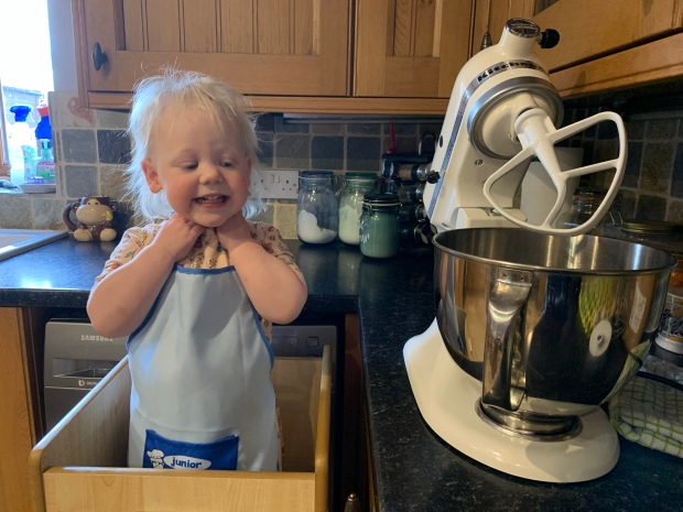 Toddler stood next to Kitchen Aid mixer looking excited